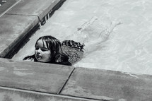 a little girl wadding in shallow water in a public pool