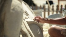 a man and woman carving a sand sculpture
