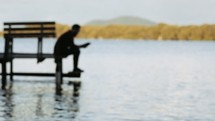 a man reading a Bible on a jetty