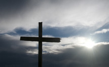 Cross against cloudy sky with sun filtering through