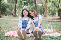 girls sitting on a picnic blanket