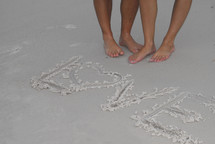 Bare feet by the waters edge with message of love written in the sand