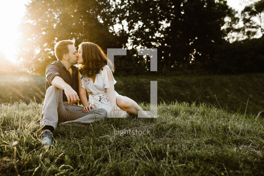 a couple sitting in the grass kissing