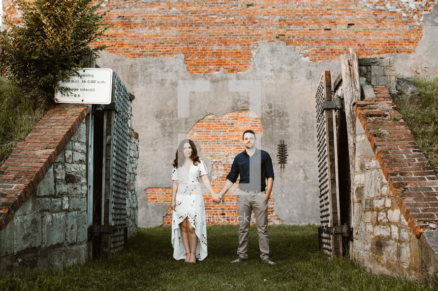 a couple holding hands standing in front of a brick wall