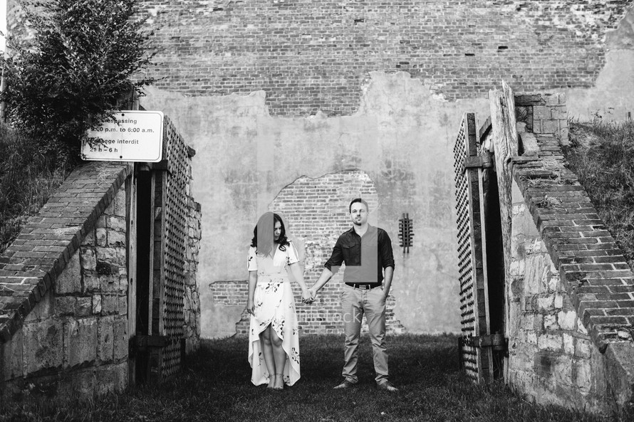 a couple holding hands standing in front of an old brick wall