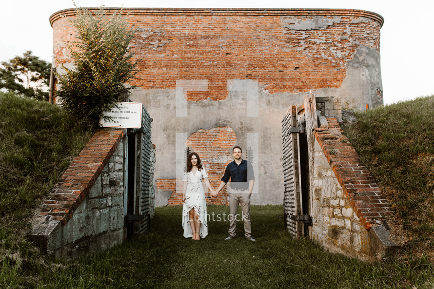 a couple standing in front of a brick building holding hands