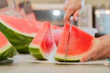 man cutting a watermelon