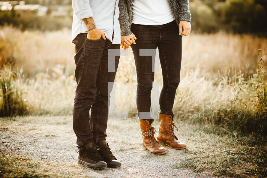 legs of a couple holding hands