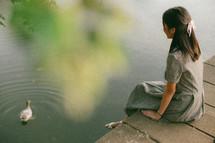 young woman sitting on a bridge feeding ducks