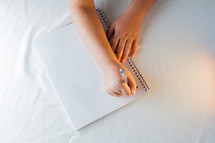 a child writing in a spiral notebook