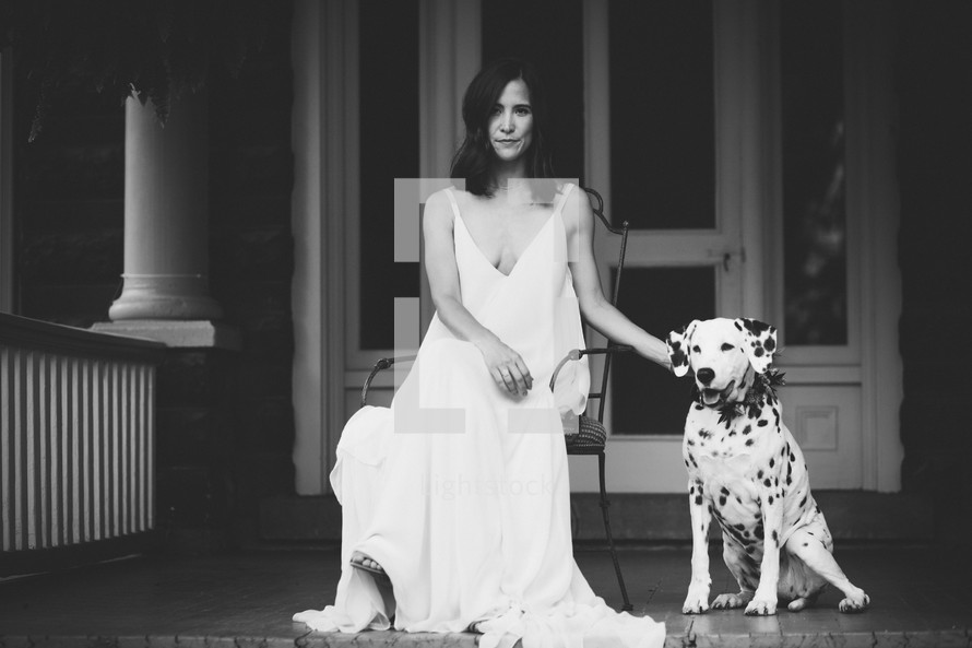 a woman sitting on a porch with her dalmatian