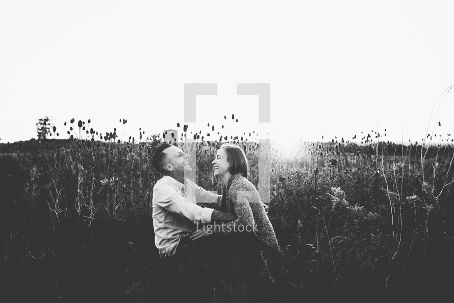 a couple sitting in a field