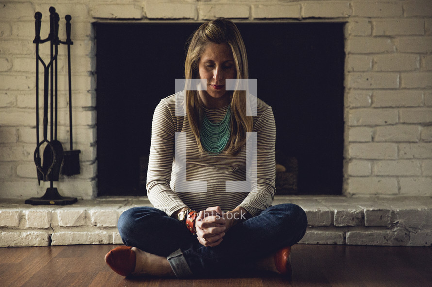 a pregnant woman praying on the floor