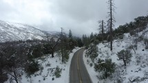 aerial view over a snowy mountain road