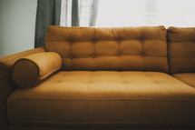 A gold upholstered couch.