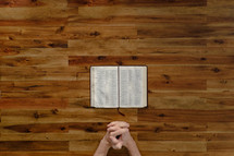 praying hands on the floor and an open Bible