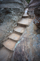 Stone stairs and steps carved between and leading through large grey and brown boulder rocks