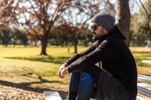 A man in workout clothes sitting in a park.