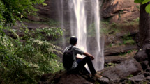 Young Man looking at waterfall.