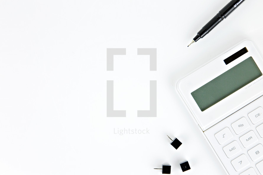 tacks, pen, and calculator on a white desk