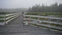 man walking over a foggy boardwalk