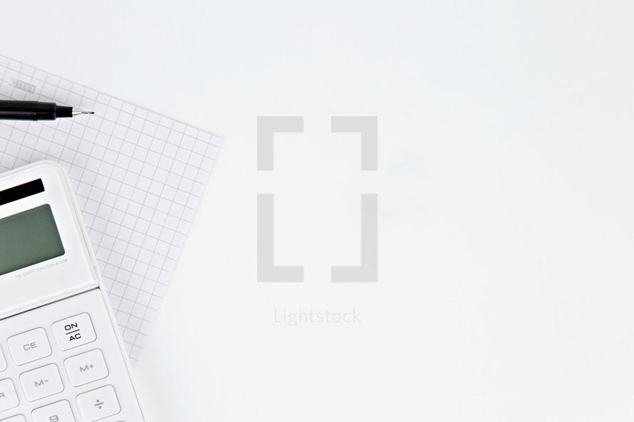 graph paper, pen, calculator on a white background