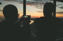 A couple taking a photo from a high rise building of the sunset.