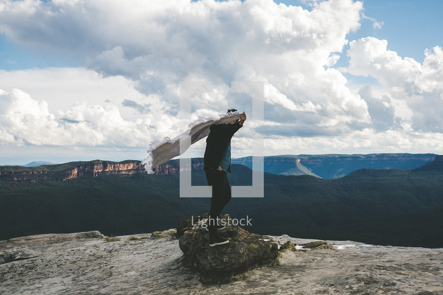 woman standing on a mountain top under a cloudy sky