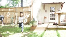 A little boy runs joyfully through the back yard into the arms of his father.