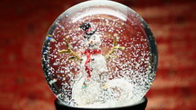 snow falling on a snowman in a snow globe