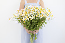 a woman holding a bouquet of white daisies