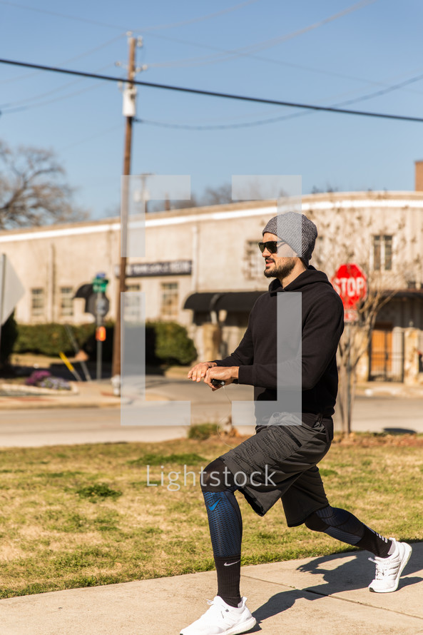 A man in workout clothes exercises outdoors.