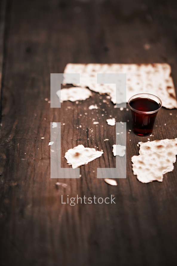 A broken unleavened cracker and communion cup filled with wine