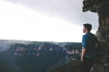 man standing on a mountain top under a cloudy sky