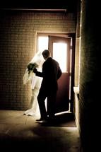 Groom holding the door open for his bride