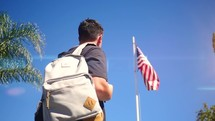 a student looks up at an American flag