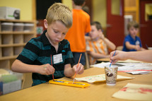 A little boy using watercolors in classroom