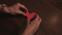 man molding a heart of clay