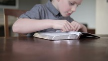 A young child reading and studying a Bible