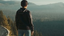 A teen standing on the edge of a mountain looking over valley forest