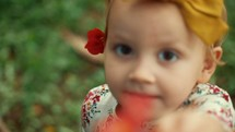 a happy toddler girl showing a flower to the camera