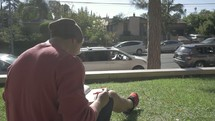man sitting in grass reading a Bible on campus