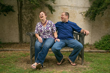 Man and woman laughing on a bench