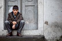 Turkish teen sitting on a door step