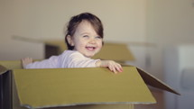 happy child playing in a cardboard box