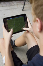 child playing soccer on a tablet