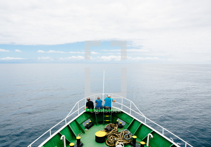 people sitting on a stern of a boat looking out