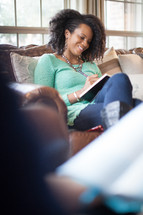 woman sitting on a couch at a Bible study writing in a journal