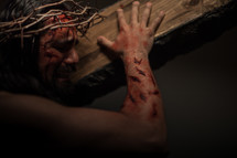 The suffering of Christ -- a beaten Jesus in His crown of thorns crying as he carries the cross.