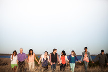 group of people walking holding hands in fellowship through a field